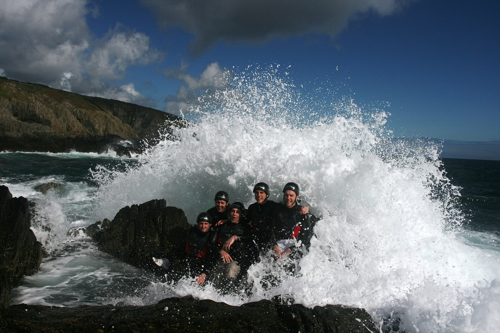 Coasteering group with large wave, Isle of Man