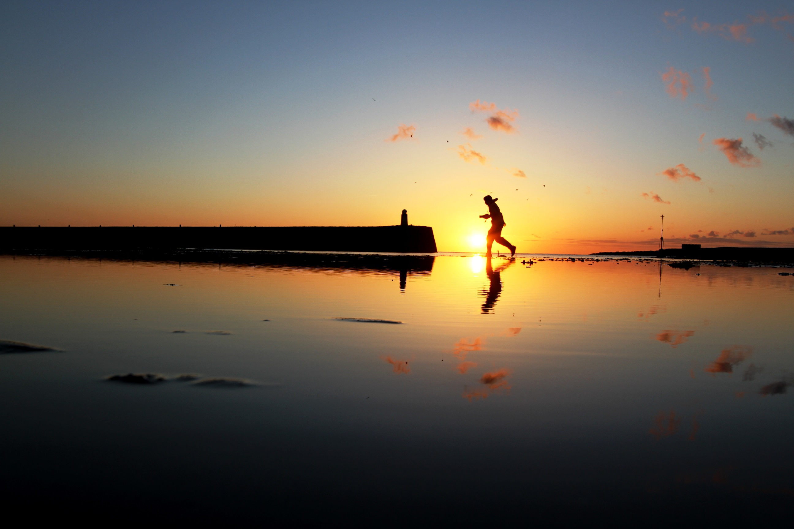 man running across water at sunrise, Isle of Man