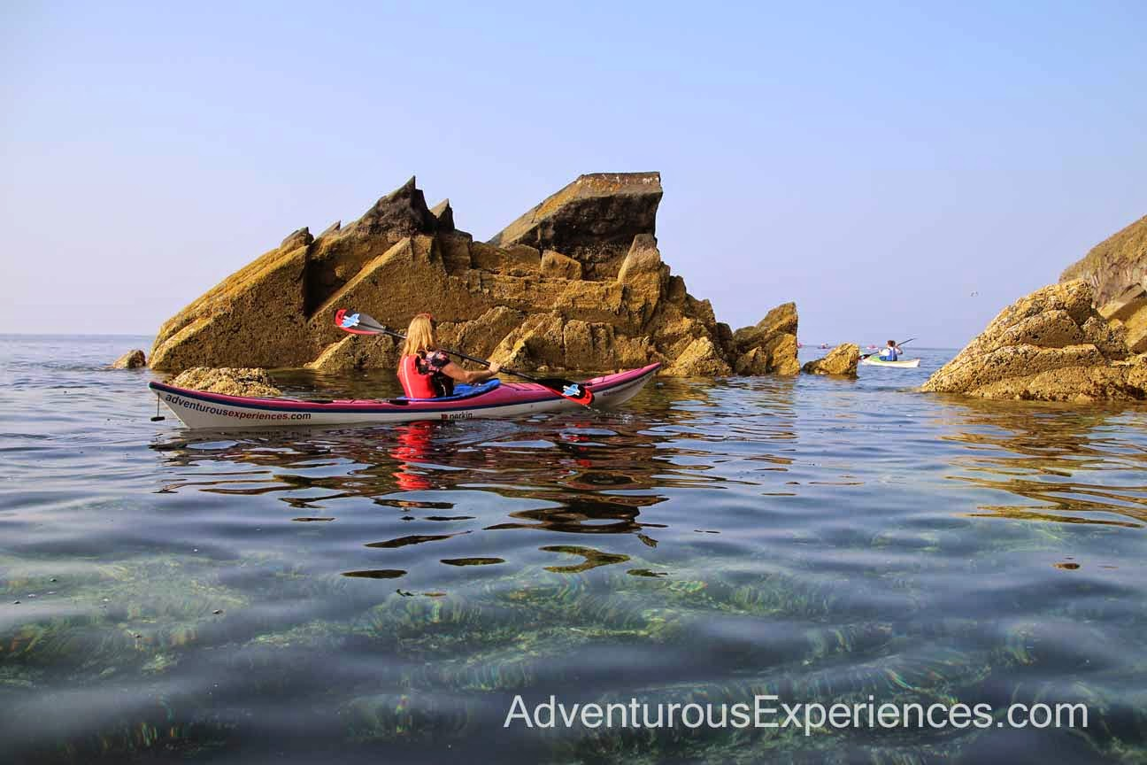 Novice kayakers paddling coastline with transparent water, Isle of Man