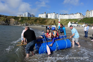 Team building group launching raft on beach, Isle of Man