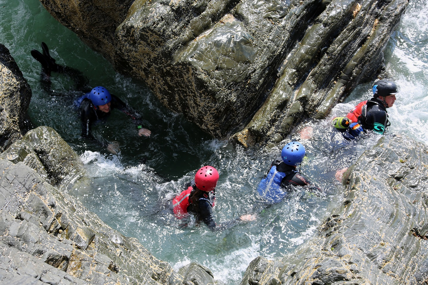 Participants swimming through a gap during a Coasteering experience, Isle of Man