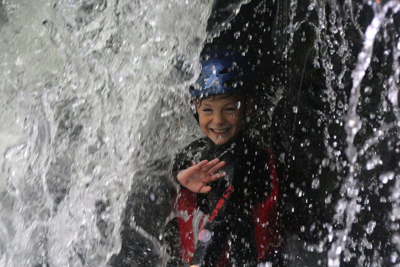Participant behing waterfall during a Gorge Scrambling experience, Isle of Man