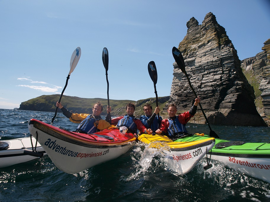 Group of sea kayakers at Sugarloaf Stack, Isle of Man