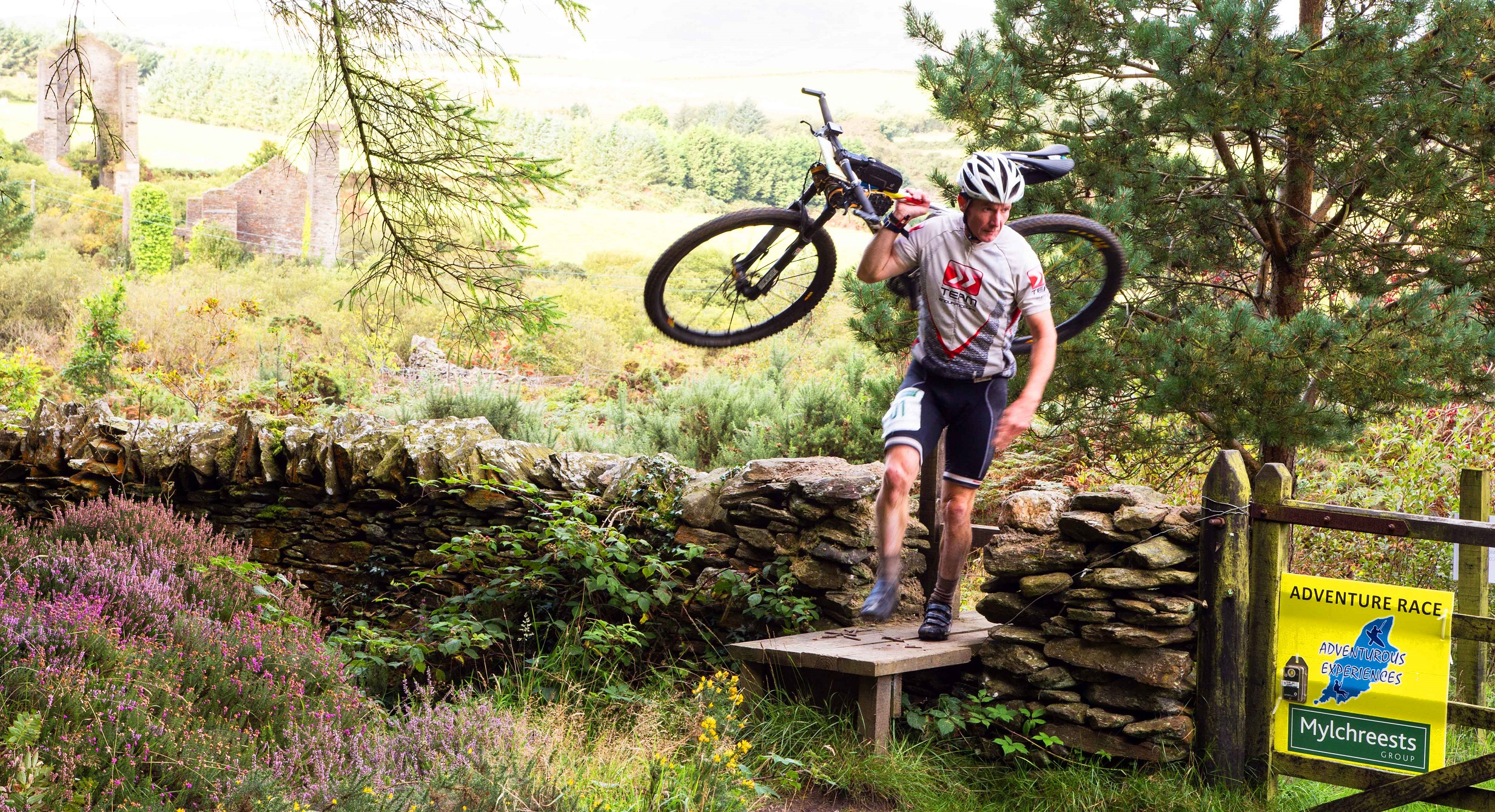Competitor lifting bike over style during Seven Kingdoms IoM Adventure Race